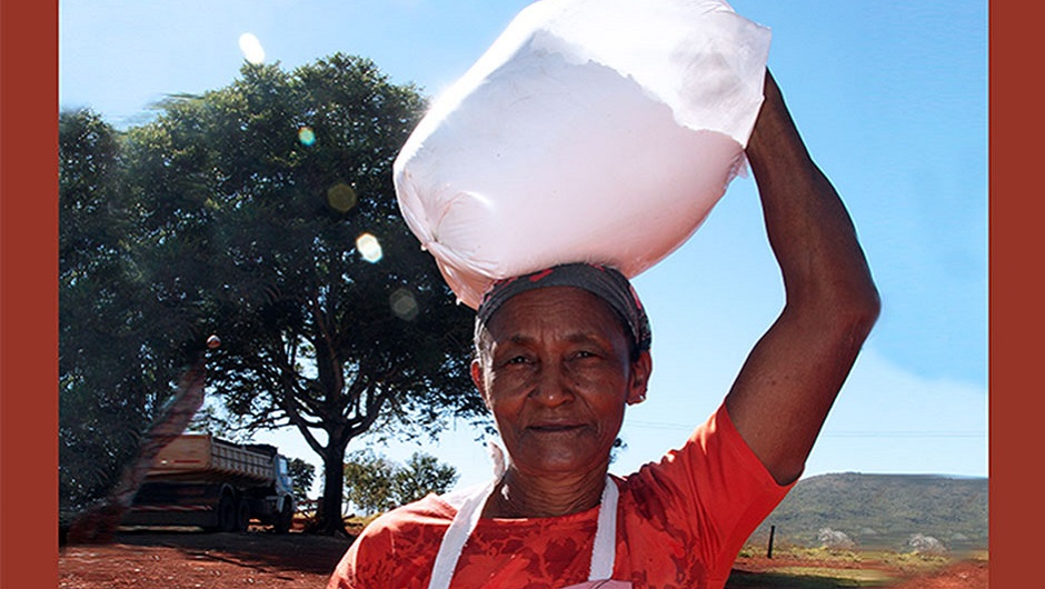 A quilombola woman carries a bag of manioc flour on her hand.