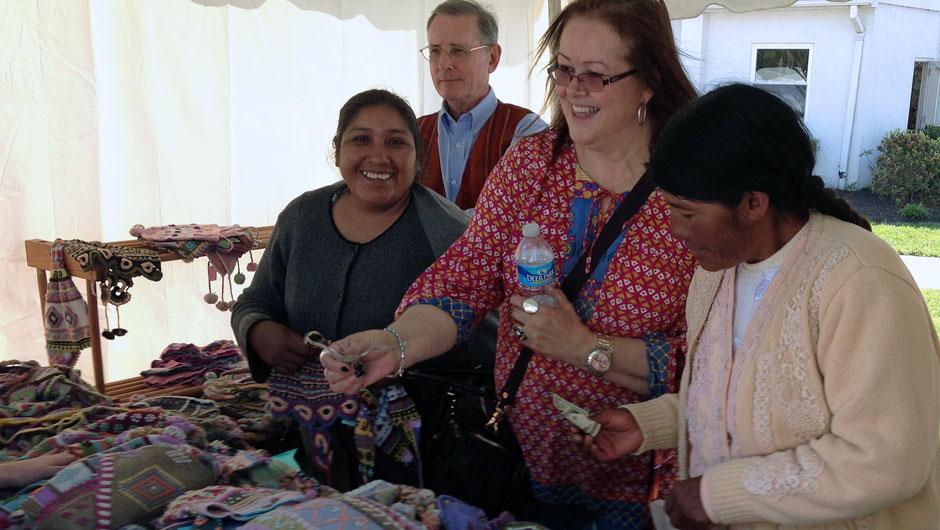 Miriam Brandao admires handmade goods while standing next to IAF grantees.