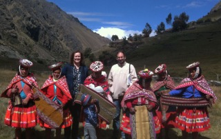 Miriam Brandao stands with a group of indigenous Peruvian women in traditional dress, in the valley between two hills.