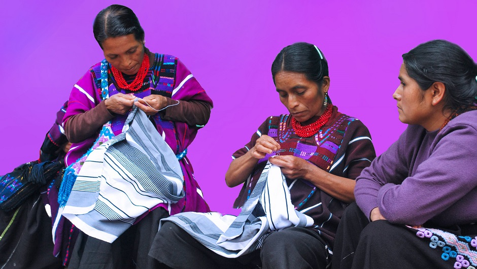 Three indigenous women sew cloths.