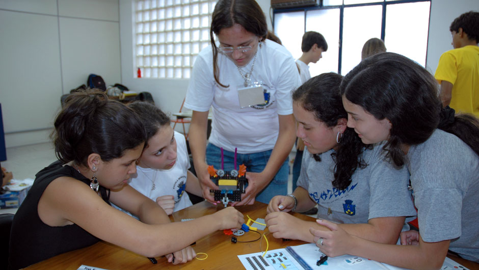 A group of young women works on a rudimentary robot.