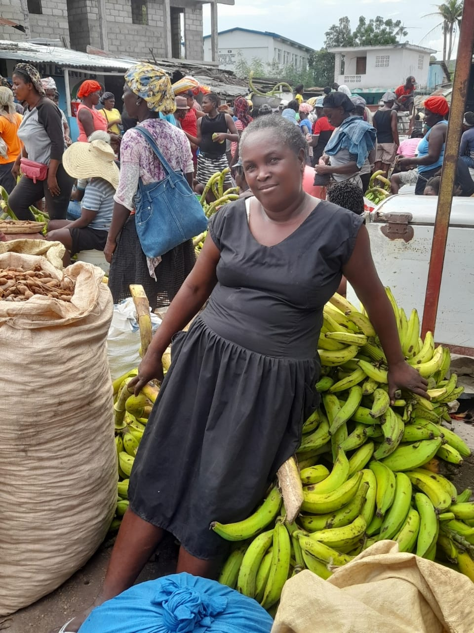 Fasemie Geffrard stands in front of a stack of bananas in a bustling outdoor marketplace in Haiti.